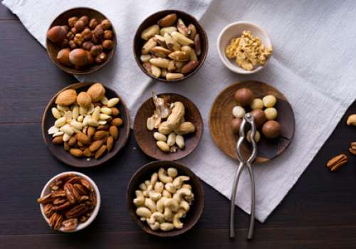 Bowls of assorted nuts in their shells.