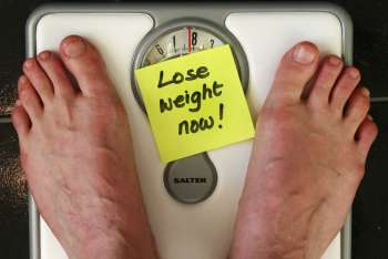 "Scale with sign, ""Lose weight now!"""
