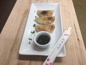 plate of chicken dumplings with sauce and chopsticks
